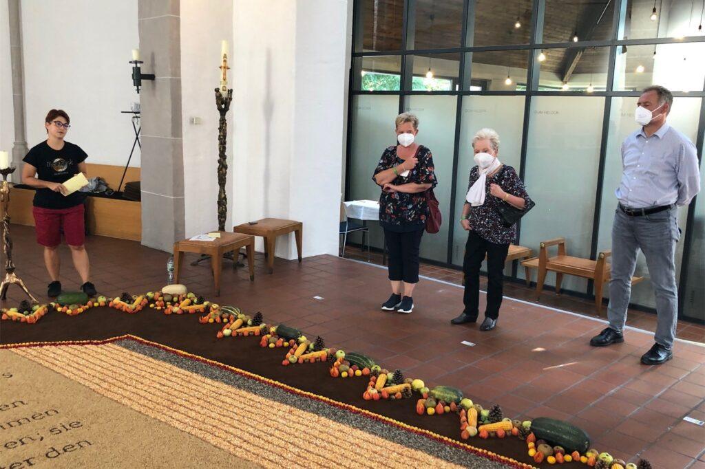 Ulrike Häusner (l.) von der Gemeinde St. Martinus, zu der die Kirche St. Maria Heimsuchung gehört, informierte die Gruppen bei der Eröffnung des Früchteteppichs 2021 über dessen Hintergründe.